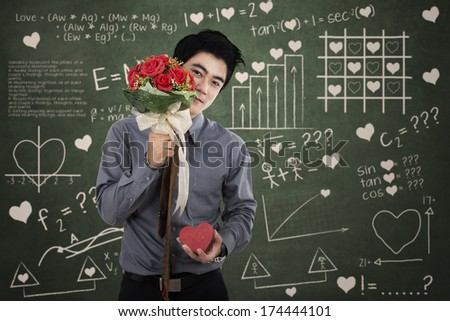 Man with a gift box and flowers standing in front of the formula of love