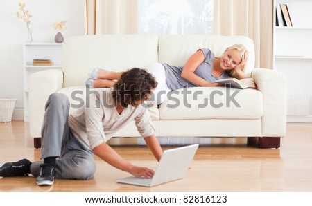 Man with a laptop while his girlfriend is holding a book in their living room