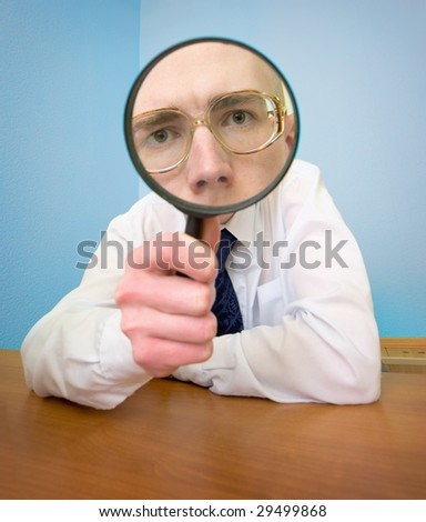 Man with a magnifier in a hand on a workplace