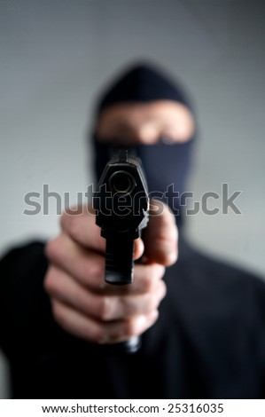 man with a mask a gun ready to use
