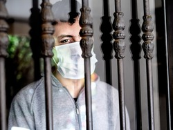 Man with a medical mask looks sadly out of the door during his confinement because of convid 19