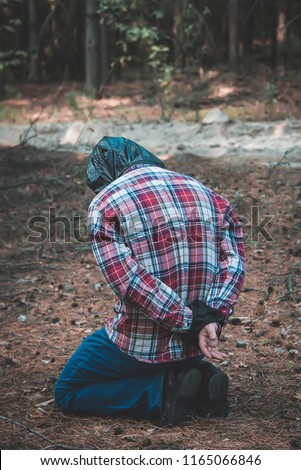 man with a package on his head in the forest. victim of crime. murder. Stockfoto ©