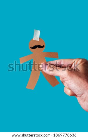 man with a paper man doll in his hand, as a prank for dia de los inocentes, the innocents day, a feast held in spain, hispanic america and philippines equivalent to april fools day, blue background Foto stock ©