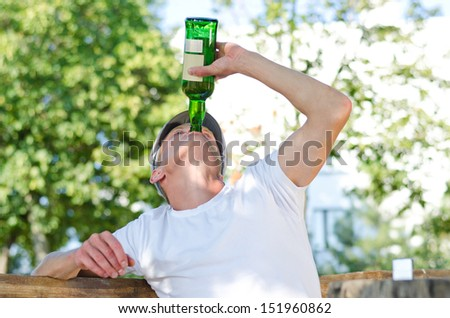 Man with a severe drinking problem upending a bottle of spirits and gulping down the alcohol as he sits outdoors under leafy green trees