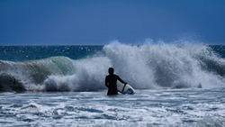 Man with a Surfing board in Shimoda Beach, Pacific Ocean, Japan