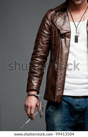 man with a syringe in handcuffs