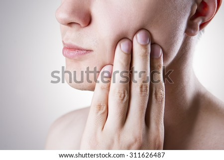 Man with a toothache. Pain in the human body on a gray background