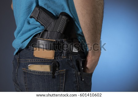 Man with a variety of everyday carry (edc) items; a gun, notes, pocket knife, and flashlight #601410602