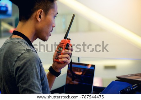 Man with a Walkie Talkie or Portable radio transceiver for communication at event #767544475
