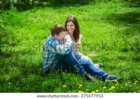 Man with a woman sitting on the grass and he kisses her hand.