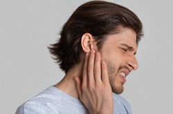 Man with ache holding ear isolated on gray background