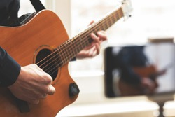Man with acoustic guitar in a shirt and cap plays music live staying home for the audience in front of the smartphone camera during quarantine and forced self-isolation due to coronavirus