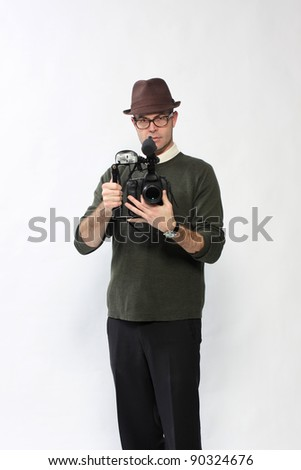 Man with an High Definition digital SLR camera with shotgun microphone and separate digital audio recorder.