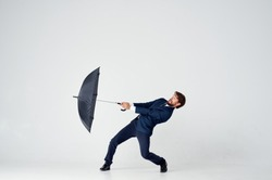 man with an open umbrella struggling with the wind