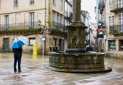 Man with an umbrella in the rain in a square with a fountain