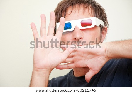 Man with anaglyph 3D glasses making funny face with his hands up.