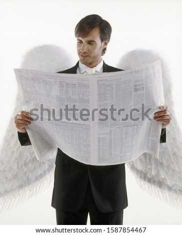 Man with angel wings reading a newspaper