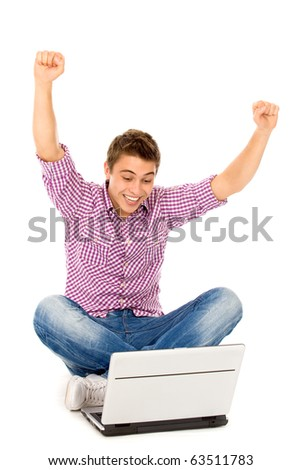Man with arms raised sitting with laptop