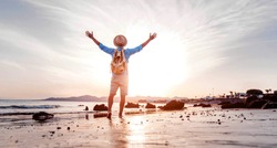 Man with arms up celebrating success in the beach at sunset - Hiker enjoying life outdoor