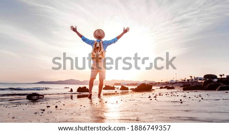 Man with arms up celebrating success in the beach at sunset - Hiker enjoying life outdoor Photo stock ©