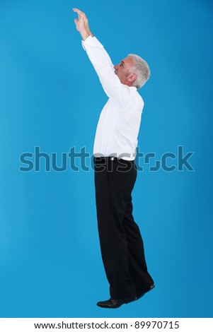 Man with arms up on blue background