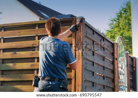 Man with artificial heart strokes a wood fence in the garden.