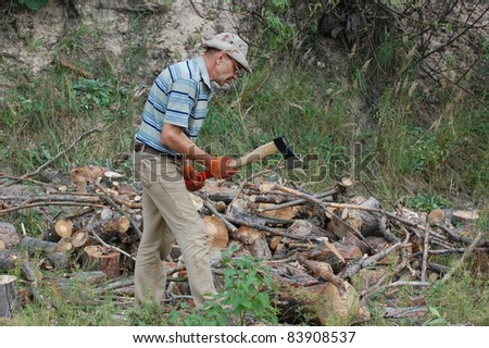 Man with axe chop logs for firewood.Ukraine