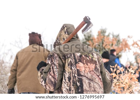 man with axe in wood. forester holding axe above the shoulder.