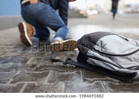 Man with backpack felling on slippery sidewalk in winter closeup Stock photo ©