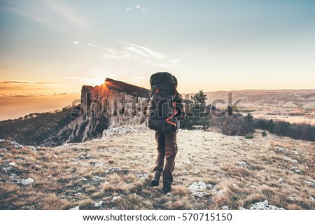 Man with backpack hiking in mountains Travel Lifestyle success concept adventure active vacations outdoor mountaineering sport sunset landscape #570715150