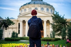 Man with backpack in front of Romanian Athenaeum ATN Academy of Theatre in Bucharest, Romania