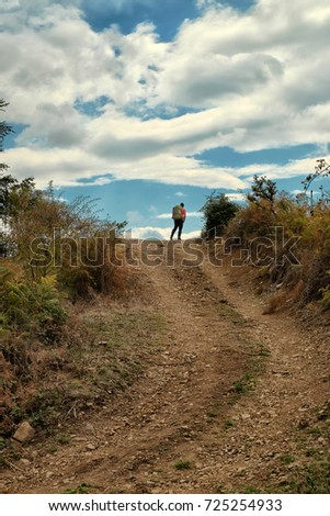 Stock Photo man with backpack on top of uphill dirt road against dramatic sky in the Nebrodi Park, Sicily