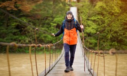 Man with backpack trekking in forest by hinged bridge over river. Cold weather. Autumn hiking. Wooden bridge across the river, Suspension bridge