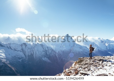 Man with backpack trekking in mountains. Cold weather, snow on hills. Winter hiking. #519426499