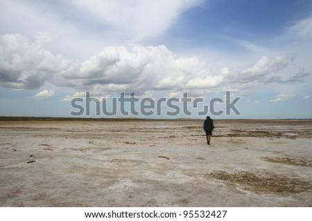 Man with backpack walking among waste landscape, salty lake Baskunckhak in summer