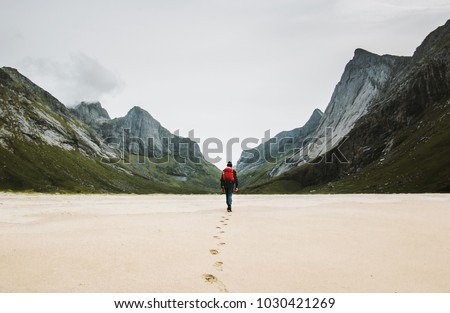 Man with backpack walking away alone at sandy beach in mountains Travel lifestyle concept adventure outdoor summer vacations in Norway wild nature  #1030421269
