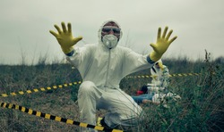 Man with bacteriological protective suit prohibiting entering cordoned off area while his partner looks at a corpse