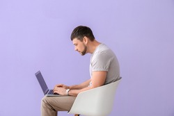 Man with bad posture using laptop while sitting on chair against color background