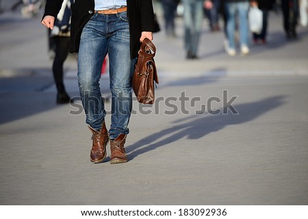 Man with bag on sidewalk in sunset, on his way home from work
