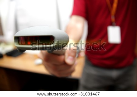 Man with bar code reader in action. Selective focus (shallow DOF).