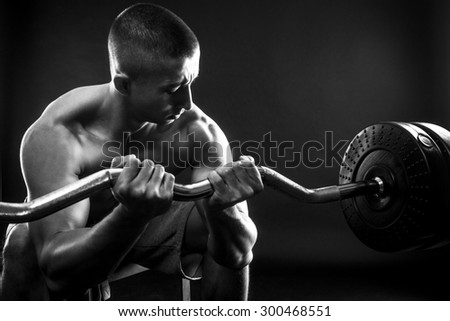Man with bare chest lift weights on black background. black and white