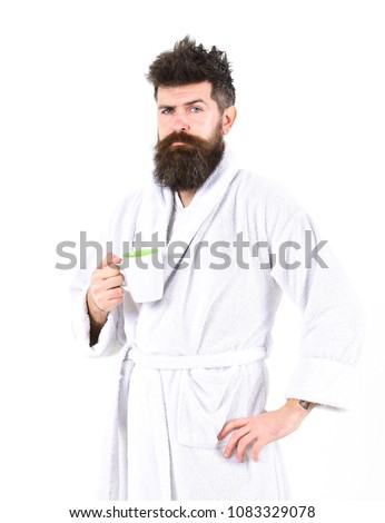 Man with beard and disheveled hair stands in bathrobe, holds mug with tea or coffee, white background. Macho drowsy, sleepy with strict face drinks coffee in morning. Morning rituals concept.