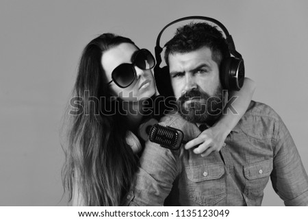Man with beard and girl hug on grey background. Pleasure, music and creative lifestyle concept. Music fans with concentrated faces wear sunglasses. Couple in love wears headphones and holds microphone #1135123049