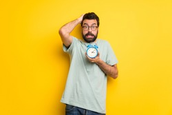 Man with beard and green shirt restless because it has become late and holding vintage alarm clock