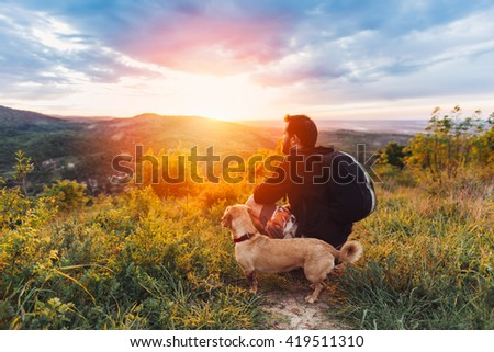 Man with beard and his small yellow dog enjoying mountain sunset and looking at the distance. He is waring black backpack and black sport sweater.