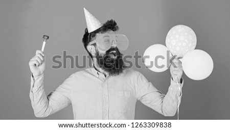 Man with beard and mustache on happy face holds air balloons, blue background. Guy in party hat with holiday attributes celebrates. Hipster in giant eyeglasses celebrating birthday. Party concept. #1263309838