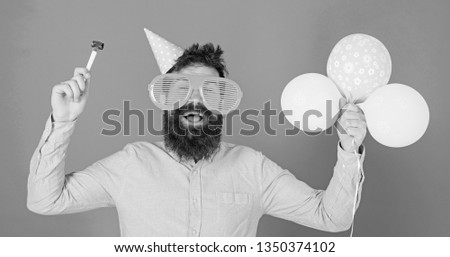 Man with beard and mustache on happy face holds air balloons, blue background. Hipster in giant eyeglasses celebrating birthday. Party concept. Guy in party hat with holiday attributes celebrates. #1350374102
