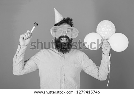 Man with beard and mustache on happy face holds air balloons, blue background. Party concept. Hipster in giant eyeglasses celebrating birthday. Guy in party hat with holiday attributes celebrates.