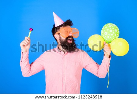Man with beard and mustache on happy face holds air balloons, blue background. Party concept. Guy in party hat with holiday attributes celebrates. Hipster in giant eyeglasses celebrating birthday. #1123248518