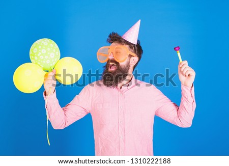 Man with beard and mustache on happy face holds air balloons, blue background. Party concept. Guy in party hat with holiday attributes celebrates. Hipster in giant eyeglasses celebrating birthday. #1310222188